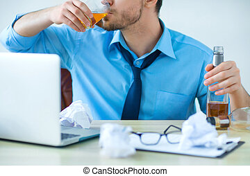 Drunk man drinking alcohol while working - Sunk in alcohol...