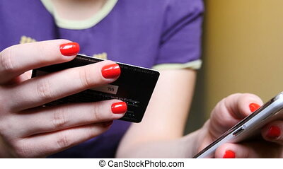 Woman using credit card and phone for online payment UltraHD...