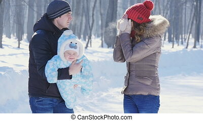 father and mother walk in park with child at winter slowmotion