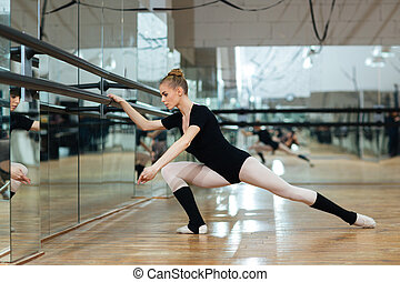 Ballerina warming up - Attractive ballerina warming up in...