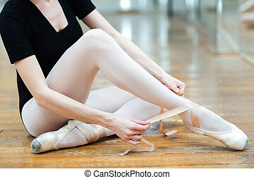 Ballerina dressing pointe shoe - Cropped image of a...