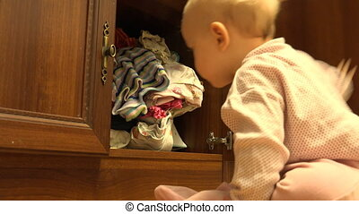 The Child Throws Clothes from the Dresser - The Child Throws...