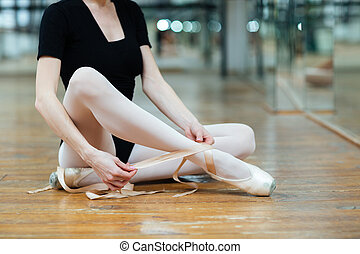 Ballerina tying pointe shoes in ballet class - Cropped image...