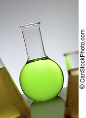 flask - laboratory flask containing green liquid on a white...