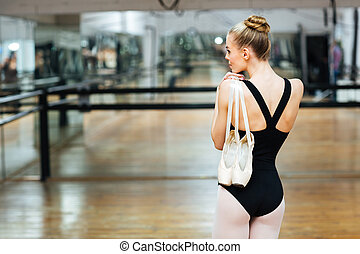 Back view portrait of a ballerina holding pointe shoes -...