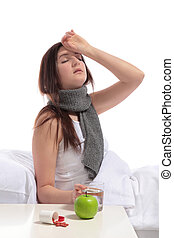 Illness - A young woman sitting in bed with a flu. All on...