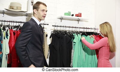 a man waits for his woman chooses a dress in a store. nervous and takes the first available clothes