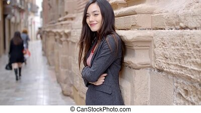 Stylish woman standing waiting in an urban alley - Stylish...