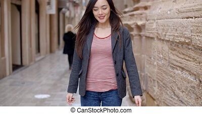 Young woman walking through an alley in town
