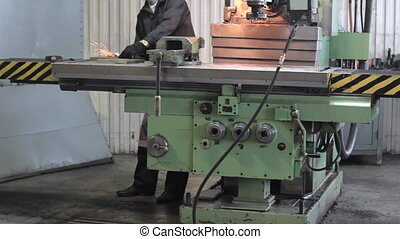 Worker on a machine lathe in factory. Machining process in...