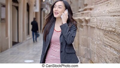 Young woman walking through town with her mobile