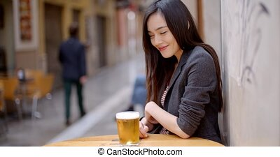 Friendly young woman sitting enjoying a beer at a table at...