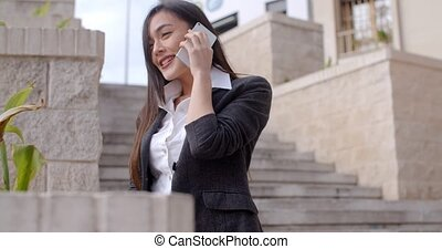 Happy young woman chatting on her mobile - Low angle view of...