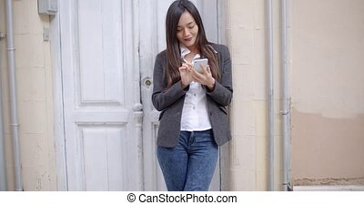 Attractive young woman sending a text message on her mobile...