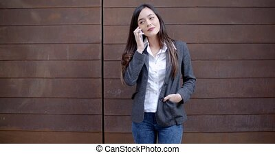 Casual relaxed young woman talking on a mobile