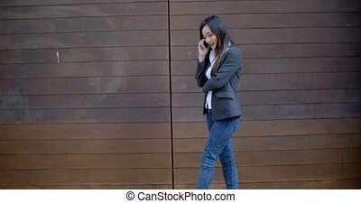 Stylish trendy woman chatting on a mobile phone as she walks...