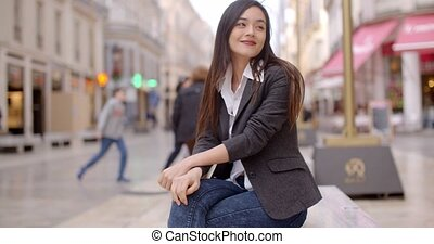 Woman sitting on a bench in town waiting - Relaxed...