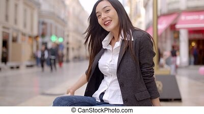 Woman sitting on a bench in town waiting