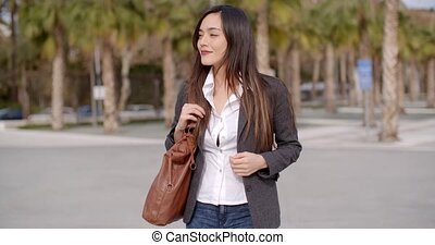 Thoughtful attractive young woman standing outdoors watching...