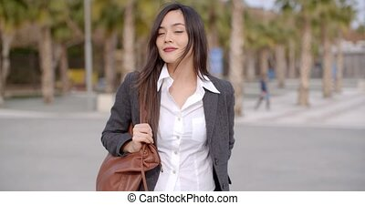 Fashionable young woman carrying a large handbag standing...
