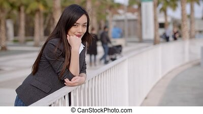 Young thoughtful woman leaning on a railing - Young...