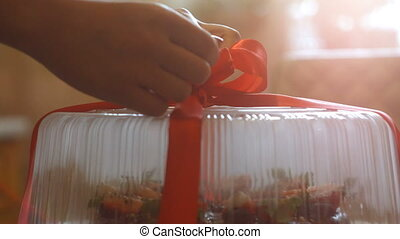decompresses the cake, unties the red ribbon slow motion -...