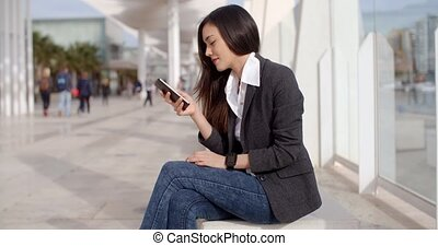 Pretty woman reading a text message on a mobile - Attractive...