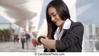 Attractive woman checking the time on her wristwatch as she...