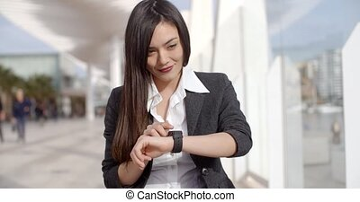 Young woman checking her wristwatch for the time as she...