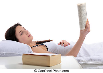 Bedtime reading - A young woman lying in her bed reading a...