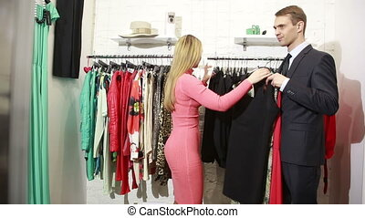 a man waits for his woman chooses a dress in a store. man...
