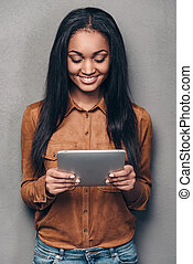 Enjoying her new digital tablet. Beautiful young African woman holding touchpad and looking at it with smile while standing against grey background