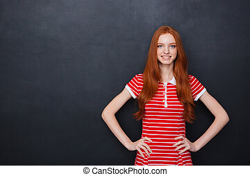 Cheerful woman standing and smiling over blackboard...