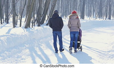 Happy young family walking in the park in winter The parents...