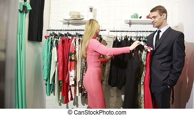 a man waits for his woman chooses a dress in a store. man holding a lot of clothes. husband wants to leave