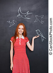 Beautiful woman holding drawn bird on blackboard background...