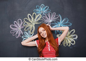 Happy woman standing over chalkboard with drawn colorful...