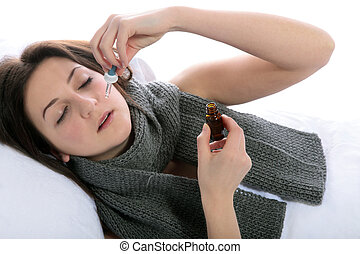 Influenza - A young woman lying in bed using nosedrops. All...