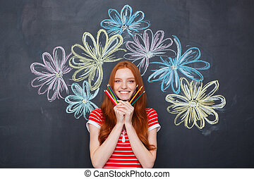 Happy woman holding pencils over blackboard background with...