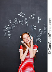 Happy woman listening to music in headphones over blackboard...