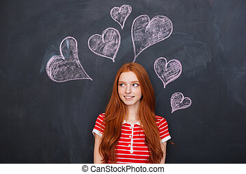 Beautiful woman standing over chalkboard with drawn hearts...