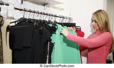 beautiful woman shopping in clothing store. chooses dress