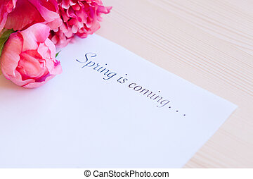 Paper with words Spring in coming and flower on the table