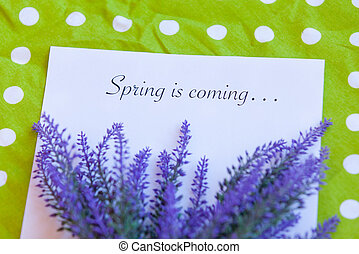Paper with words Spring in coming and flower on a napkin