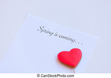 Paper with words Spring in coming and heart shape cookie