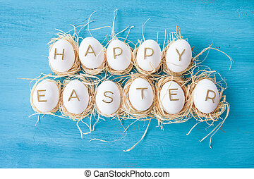 Chicken eggs with easter greeting on blue wooden background