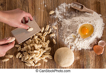 Homemade pasta rigate with egg, flour on a wood table,...