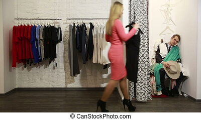 a man waits for his woman chooses a dress in a store nervous...