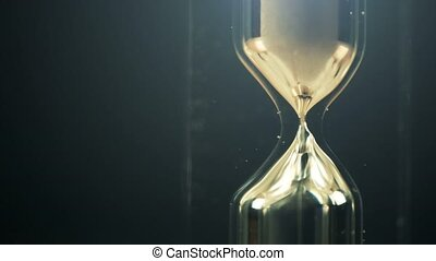 Hourglass macro shot in dark interior, passing of time...