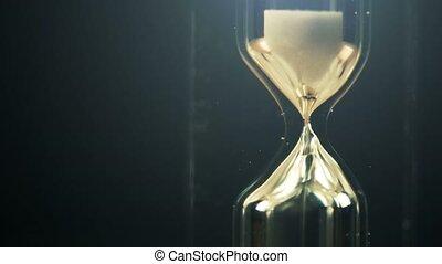 Hourglass macro shot in dark interior, passing of time...